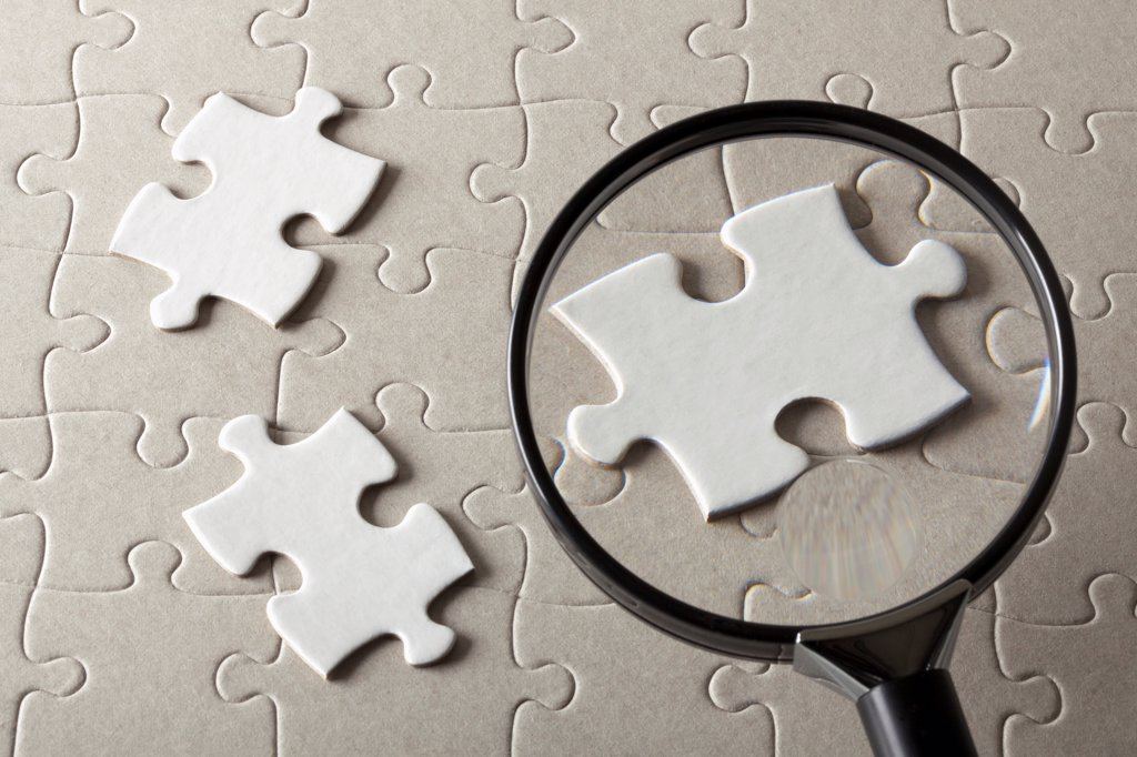 Puzzle pieces on a jigsaw puzzle being magnified by a magnifying glass : Stock Photo