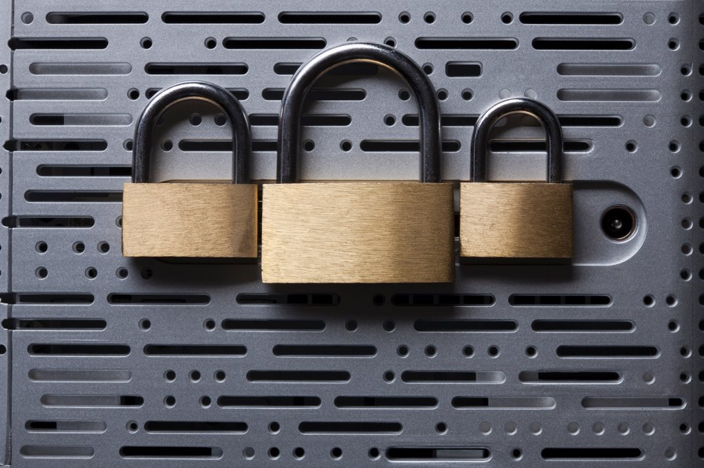 Three padlocks lying on the back of a computer hard drive : Stock Photo