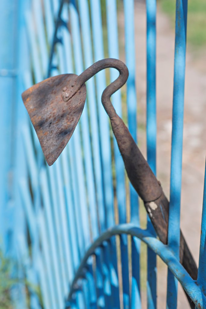 A garden hoe leaning on a gate : Stock Photo
