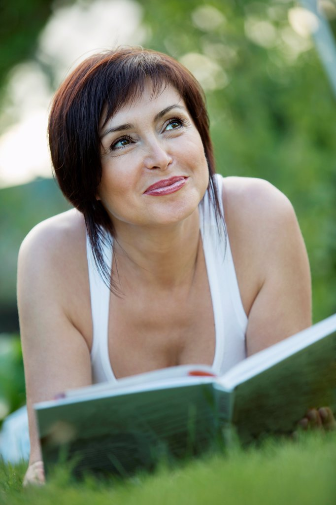 A mature woman lying down on grass with a book : Stock Photo