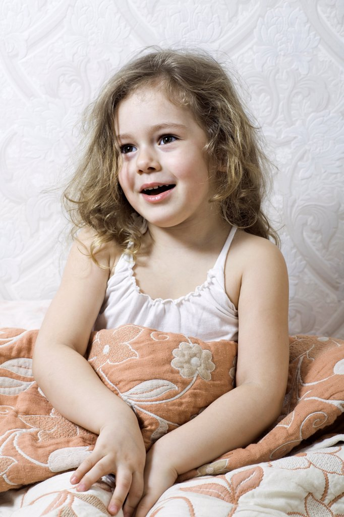 Stock Photo: 1570R-141063 A young girl sitting under a blanket