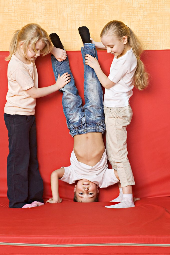 Two girls holding a boy upside down : Stock Photo
