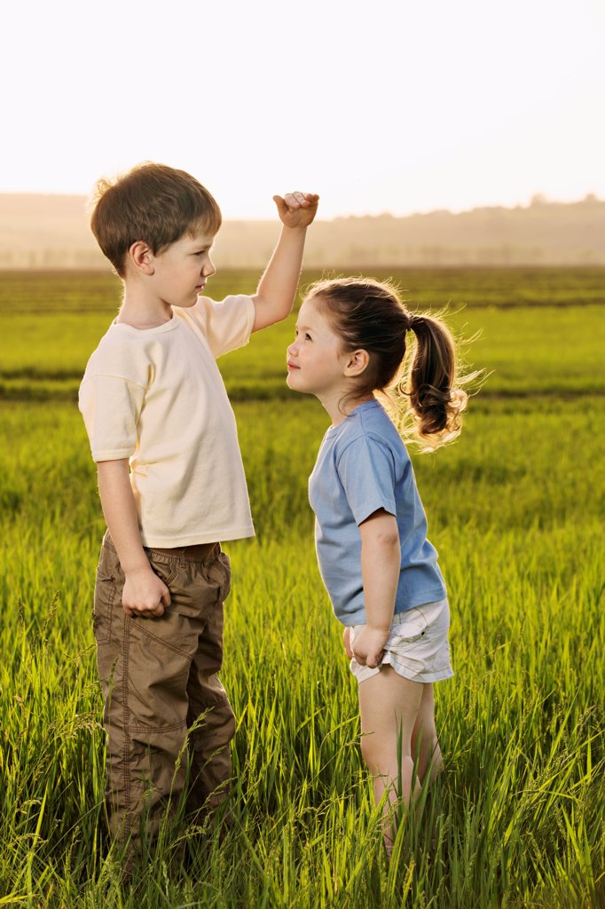 A boy and a girl in a field comparing heights : Stock Photo