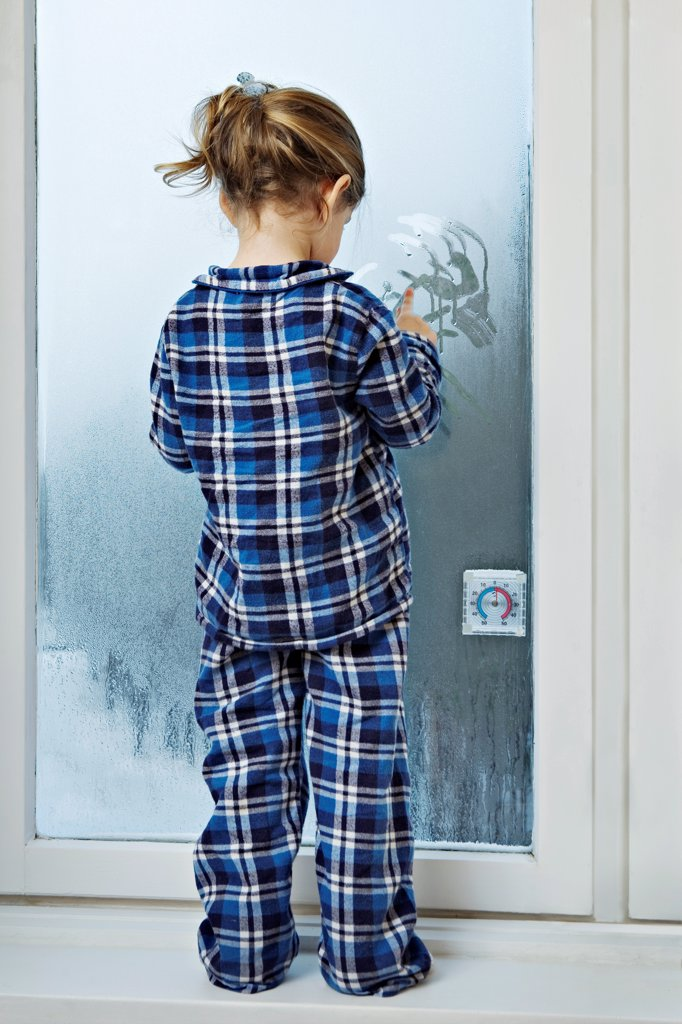 Stock Photo: 1570R-141125 A girl dressed in pajamas and drawing in condensation on glass
