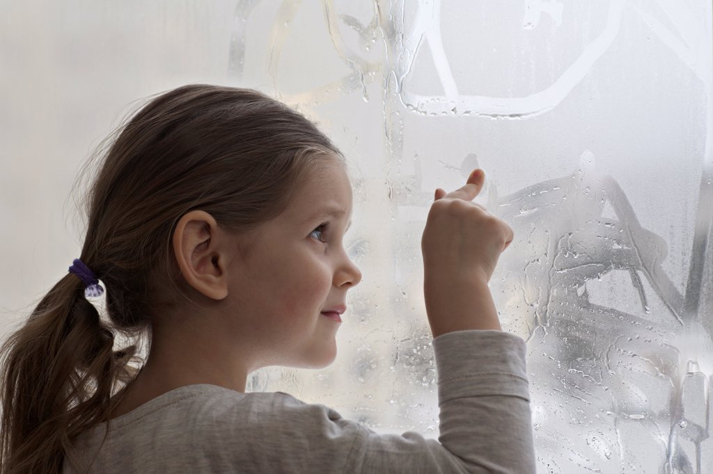 A girl drawing in condensation on glass : Stock Photo