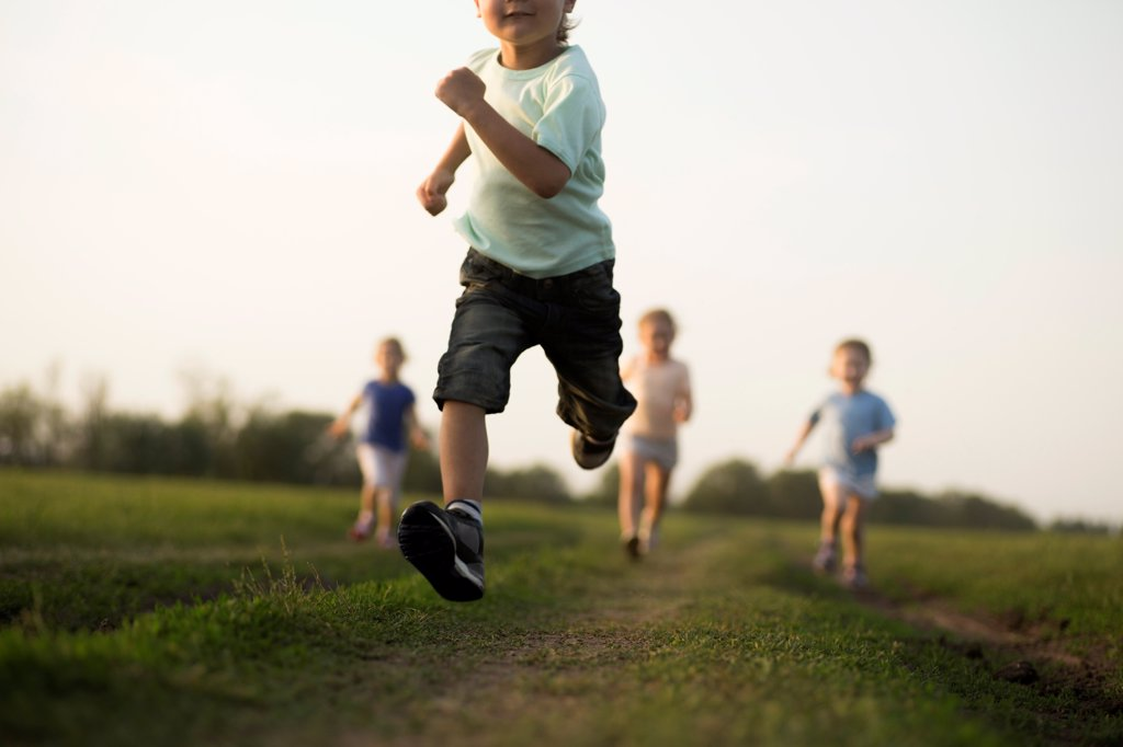 Low view of a boy running in a field with other children behind : Stock Photo