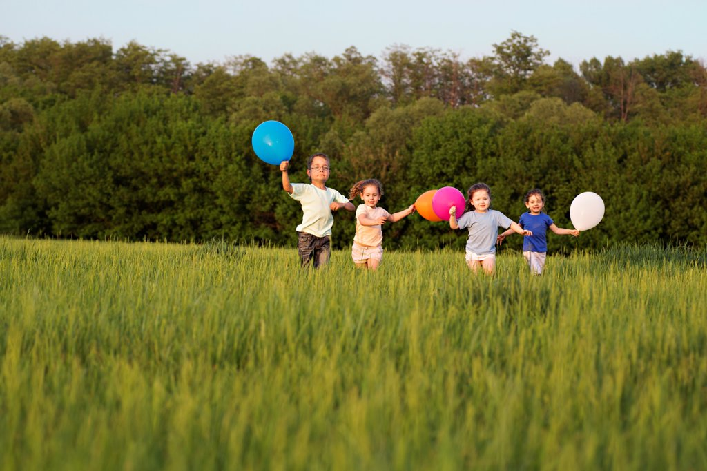 Children running in a field with balloons : Stock Photo