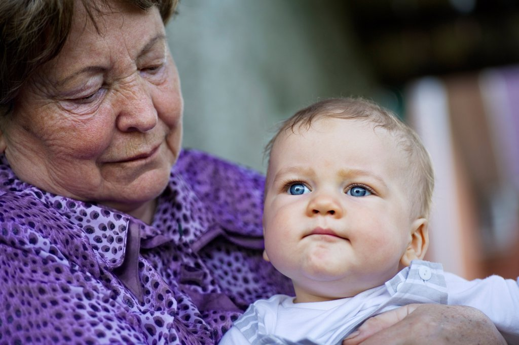 A senior woman holding a baby : Stock Photo