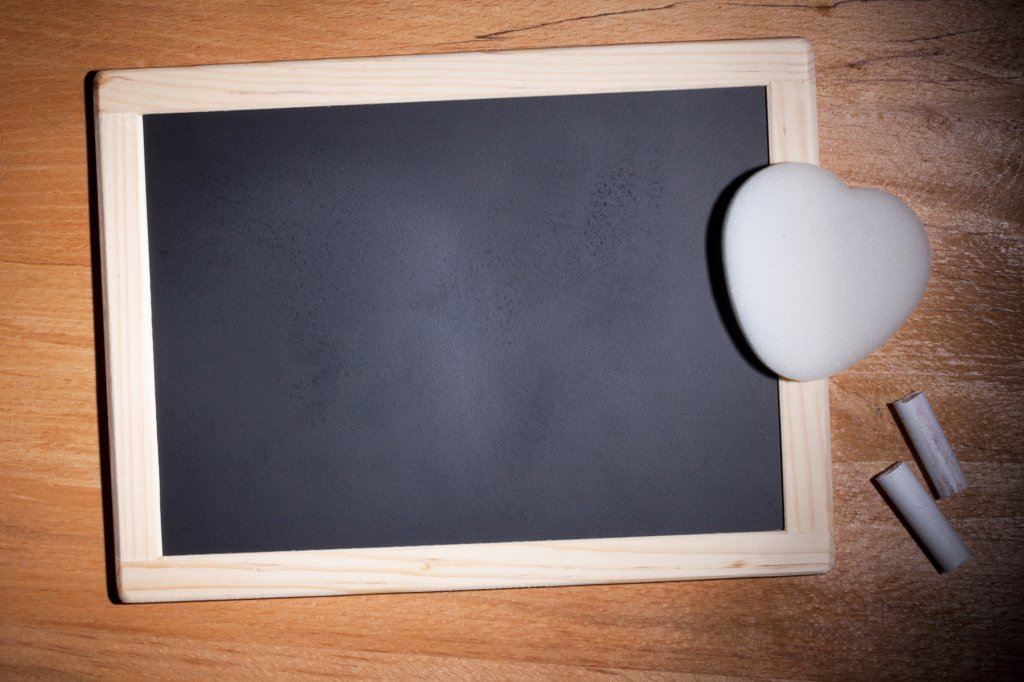 Stock Photo: 1570R-141177 A small blank chalkboard with chalk and a heart shaped eraser