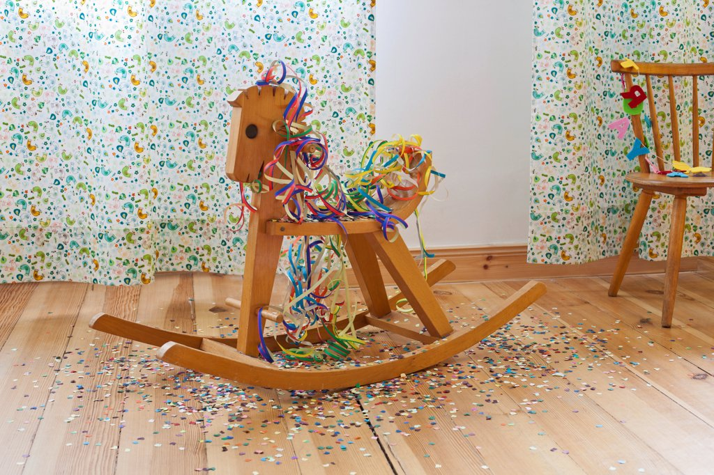 Stock Photo: 1570R-141185 A rocking horse amongst streamers, confetti and happy birthday banner