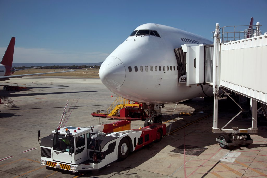 Jumbo jet attached to boarding bridge with tug in front : Stock Photo