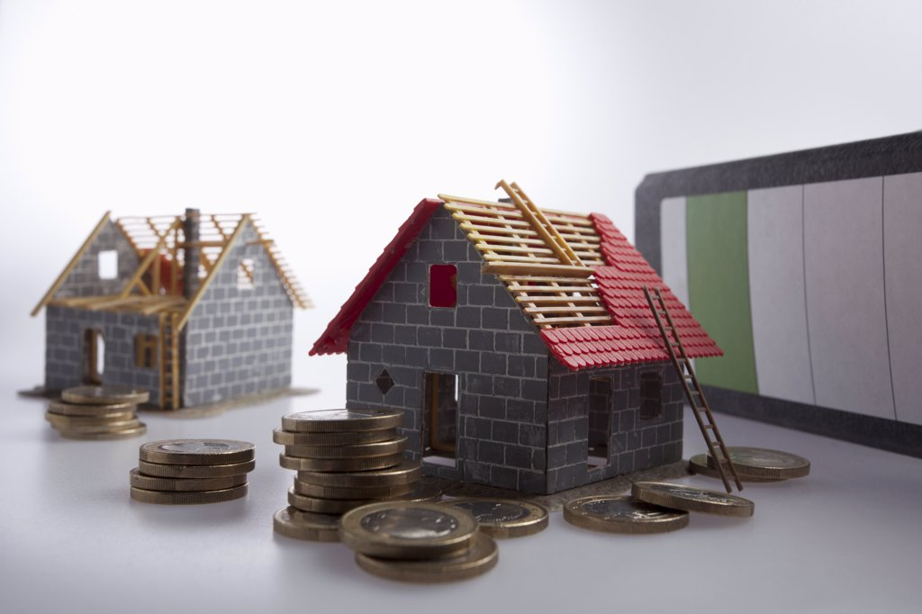 Stock Photo: 1570R-141526 Two partially constructed models of a house with piles of European Union coins around them