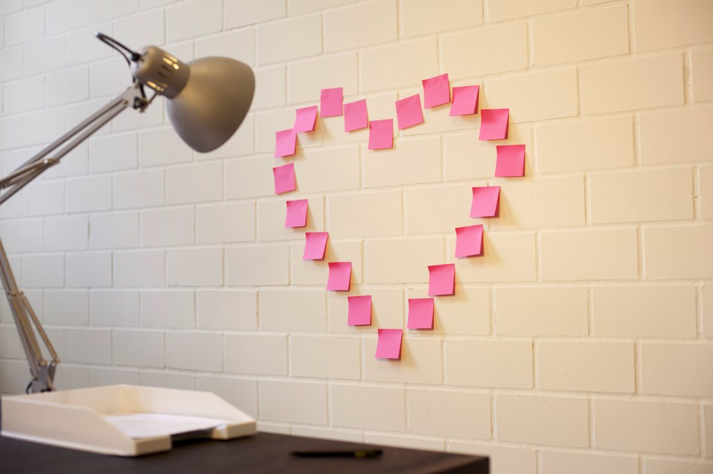 Adhesive notes arranged into the shape of a heart on a wall next to a desk : Stock Photo