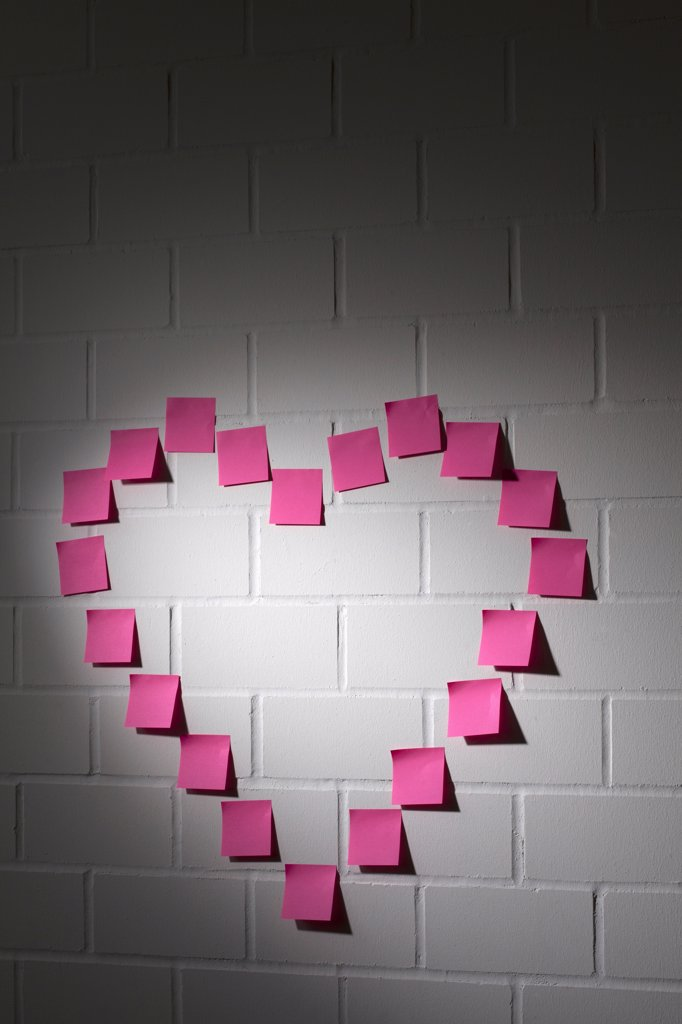 Stock Photo: 1570R-141538 Blank adhesive notes arranged into the shape of a heart on a brick wall