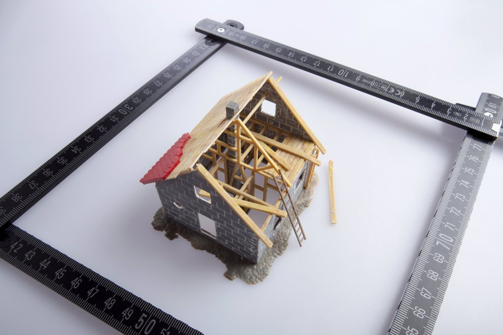 A partially constructed model of a house and a folding ruler : Stock Photo