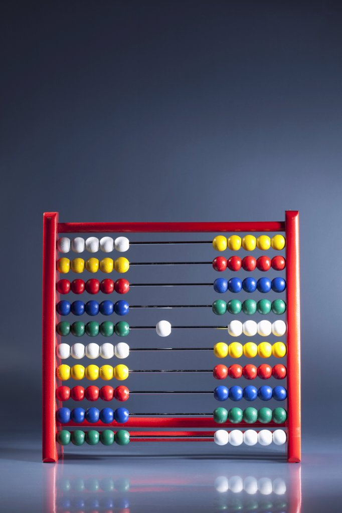 Stock Photo: 1570R-141573 An abacus with neat rows of multi colored beads and a single white bead in the middle