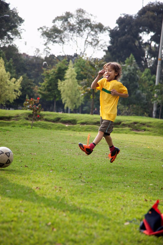 Stock Photo: 1570R-141618 A young boy jumping in mid-air on a soccer field