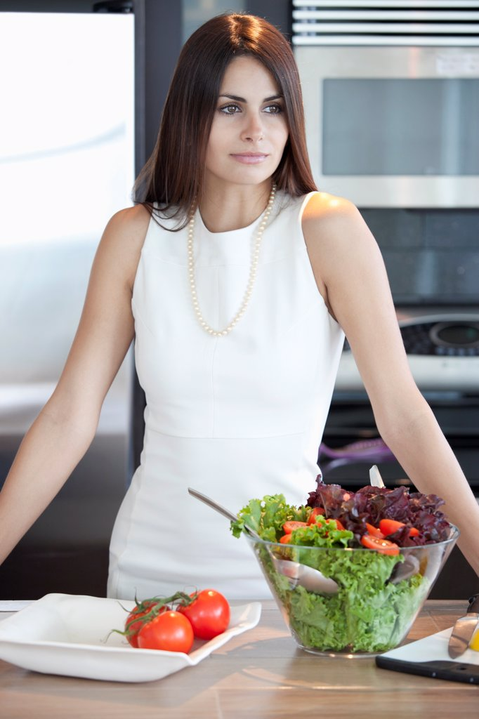 Stock Photo: 1570R-141641 Elegant woman in kitchen with bowl of salad