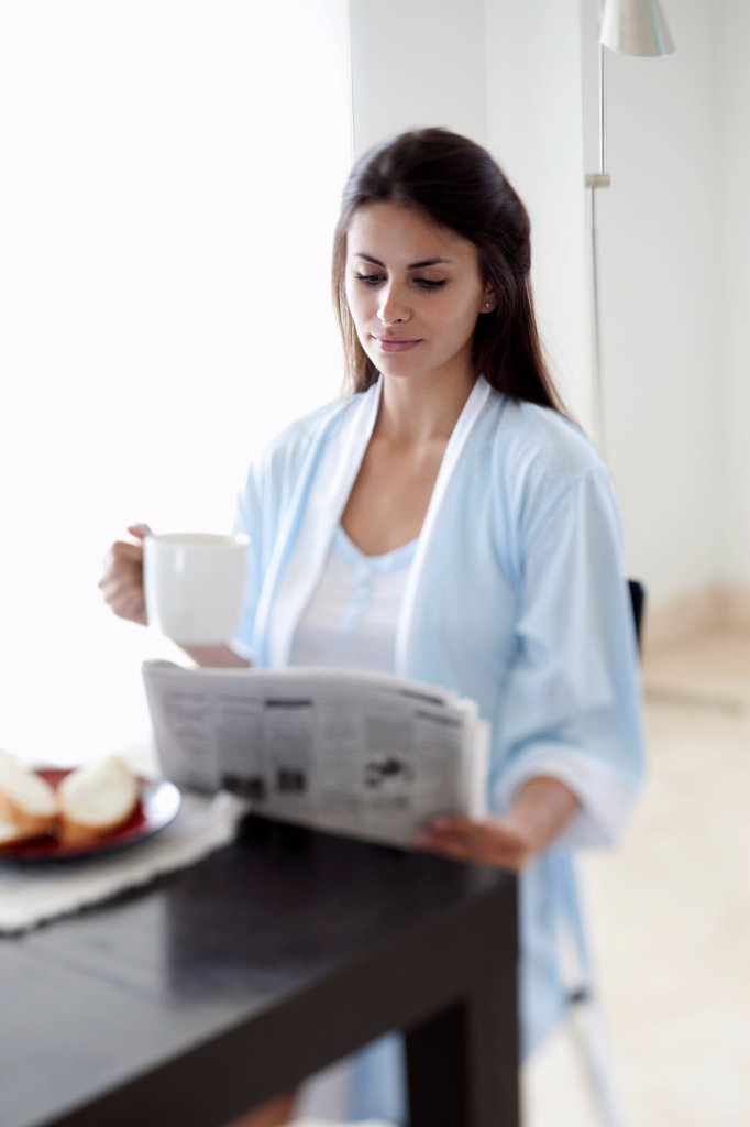 Stock Photo: 1570R-141649 Woman reading the morning newspaper