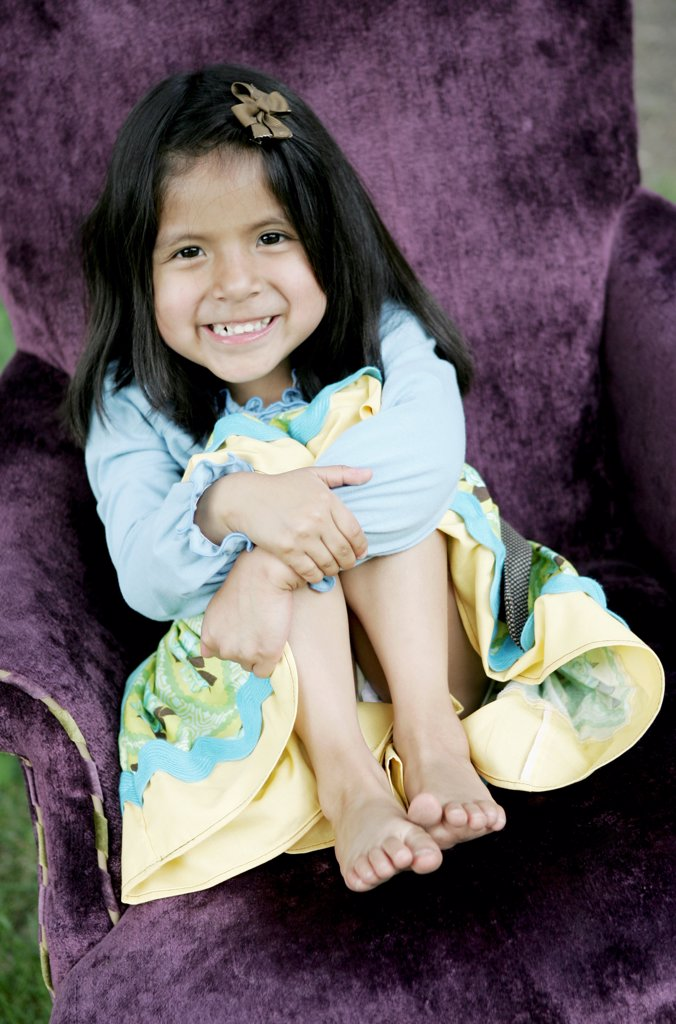 Stock Photo: 1570R-141790 A young smiling girl sitting in a purple armchair