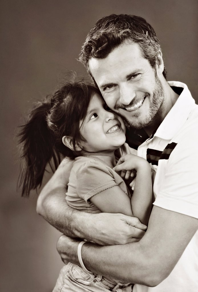 Stock Photo: 1570R-141796 A man embracing his young daughter, studio shot