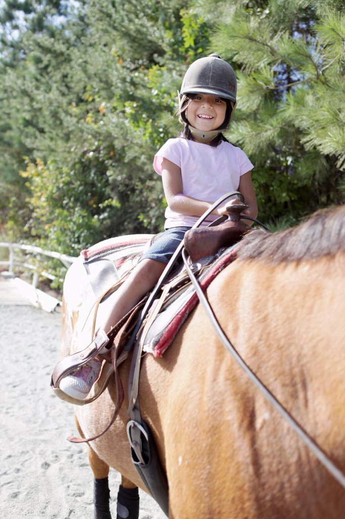 A young girl on horseback : Stock Photo
