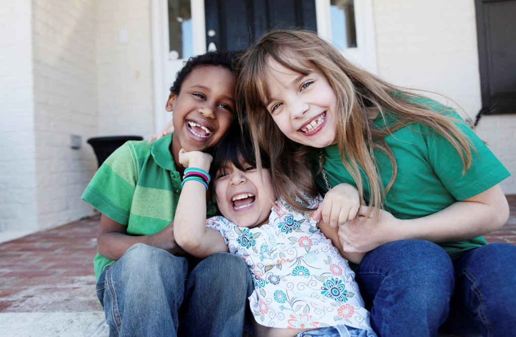 Three kids laughing affectionately while sitting on the front stoop : Stock Photo