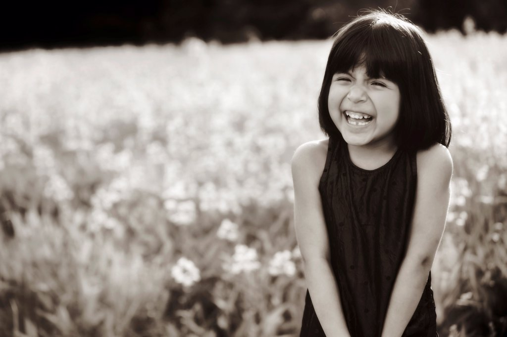 A young girl in a field laughing in the sunlight : Stock Photo