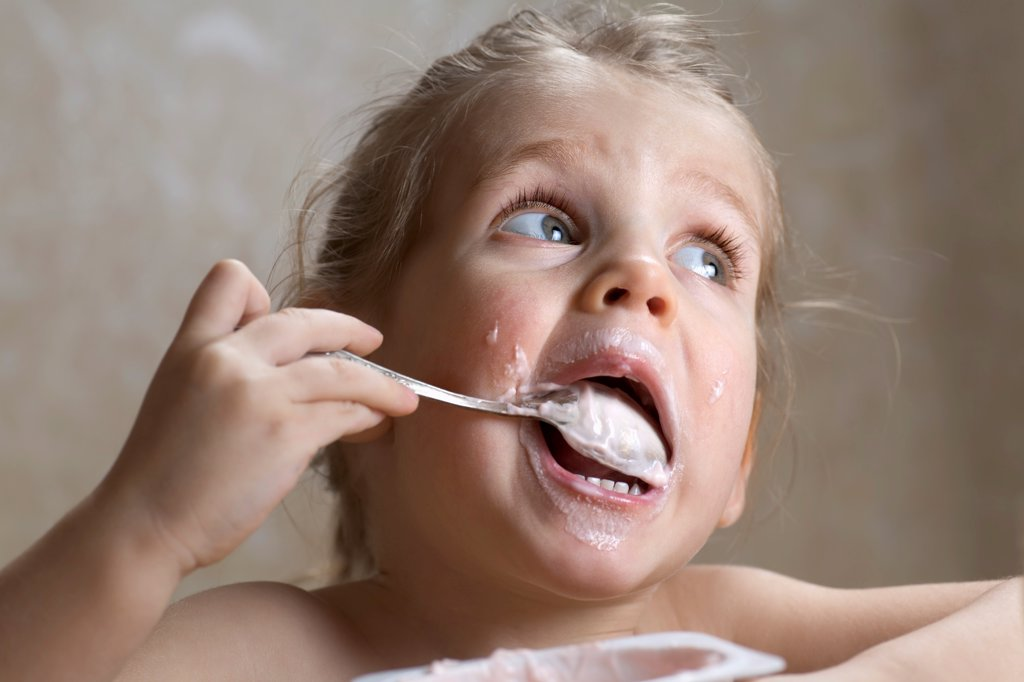 Stock Photo: 1570R-141833 A young girl making a mess out of eating yogurt