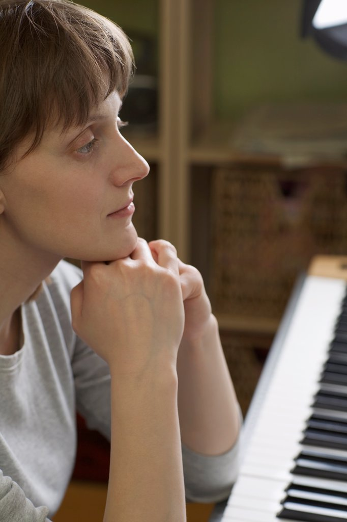 Stock Photo: 1570R-141843 A woman leaning on an upright piano, looking pensive