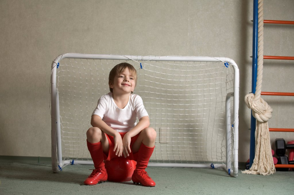 A young boy sitting on a soccer ball in front of a soccer goal : Stock Photo