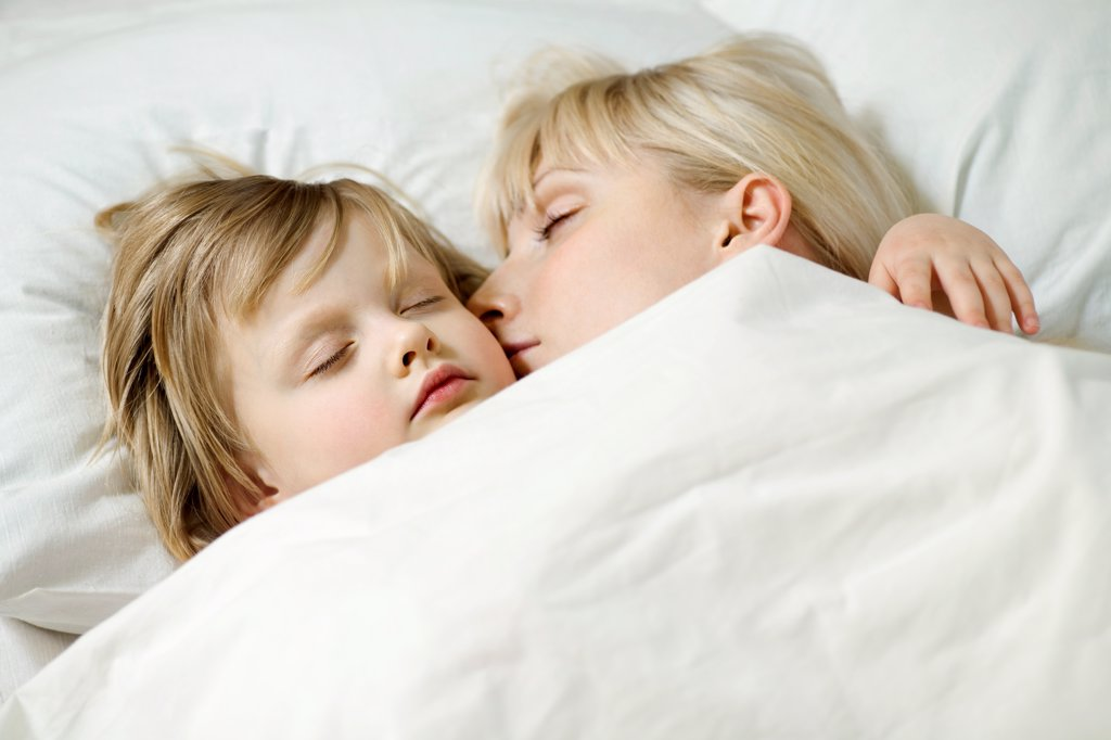 A mother and her young daughter sleeping a bed side by side : Stock Photo
