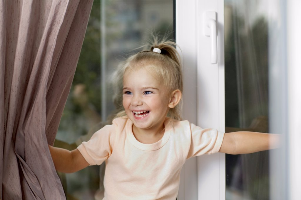 Stock Photo: 1570R-141875 A young laughing girl pushing window curtains apart