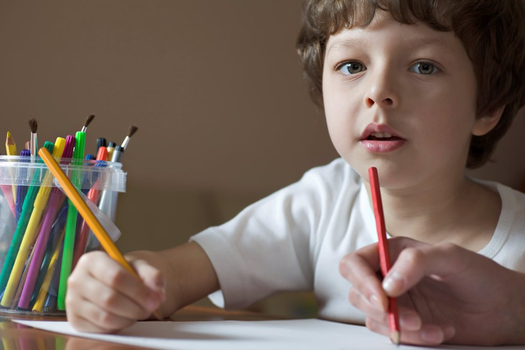 A young boy drawing with a friend, viewpoint of boy : Stock Photo