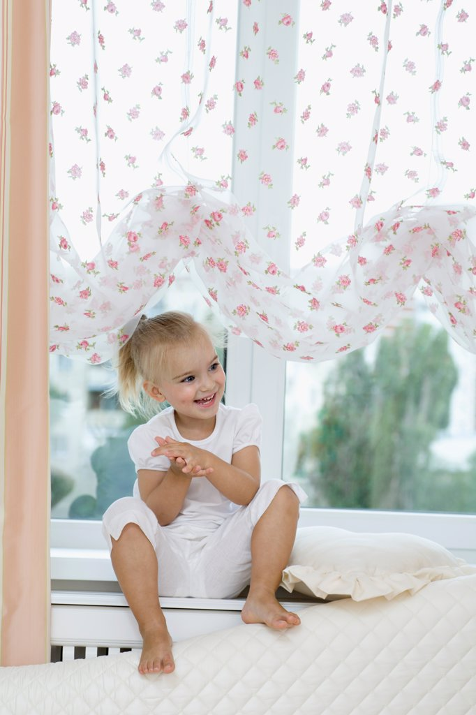 Stock Photo: 1570R-141897 A young girl sitting on a window sill, clapping hands excitedly