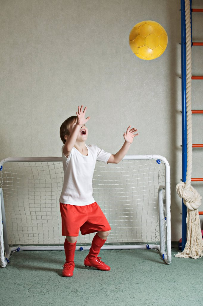 A young boy defending a goal while a ball flies towards him : Stock Photo