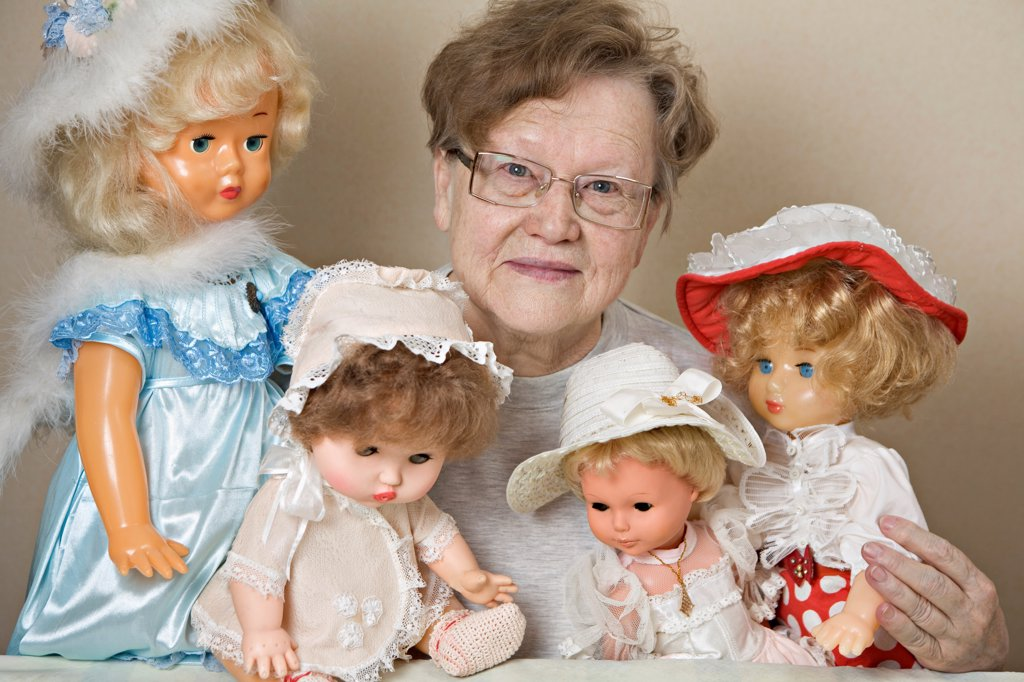 Stock Photo: 1570R-141909 A senior woman with her collection of old-fashioned dolls