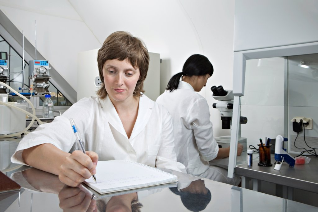 Stock Photo: 1570R-141915 A lab technician writing notes while another technician works in background