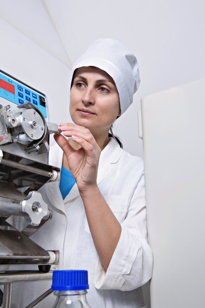 Stock Photo: 1570R-141916 A lab technician adjust a knob on diagnostic medical equipment