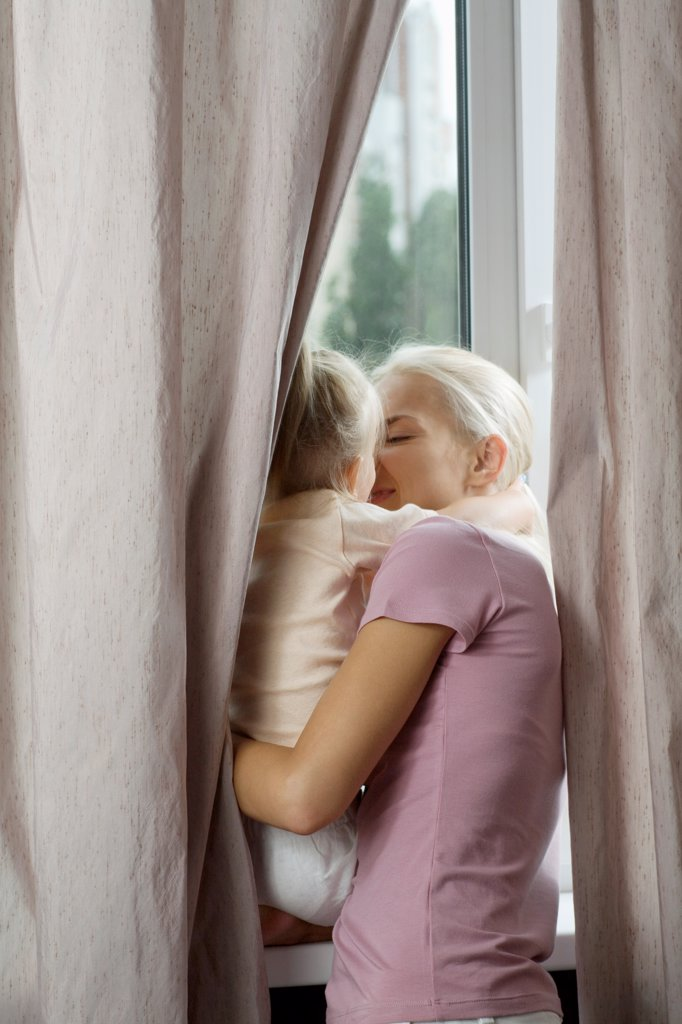 Stock Photo: 1570R-141924 An affectionate mother and daughter at a window