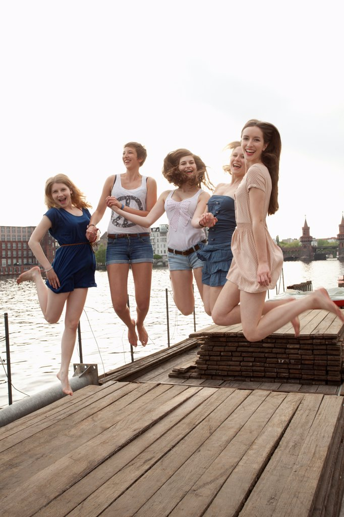 Stock Photo: 1570R-141932 Five young female friends jumping in the air on a jetty next to the Spree, Berlin, Germany
