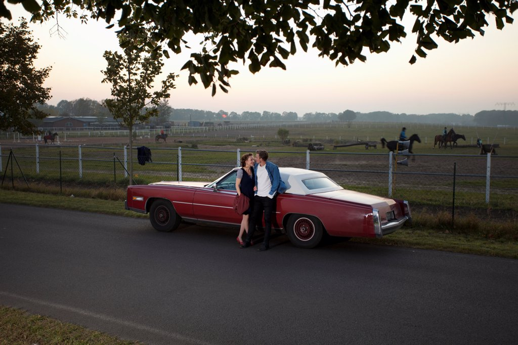 Stock Photo: 1570R-141951 A rockabilly couple leaning against a vintage car in the country