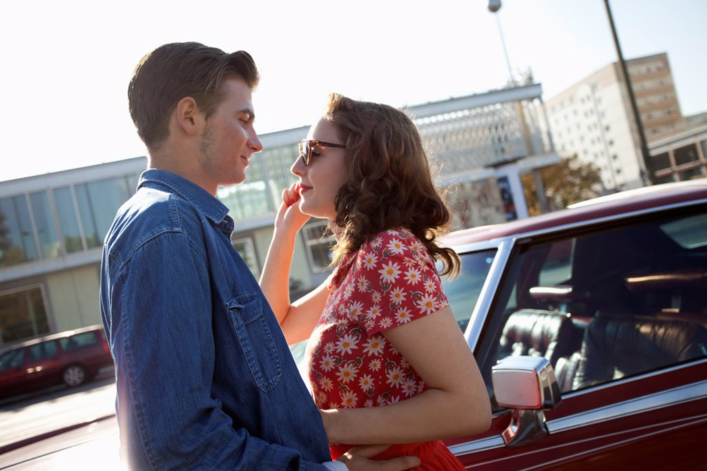 Stock Photo: 1570R-141953 A rockabilly couple standing face to face next to a vintage car