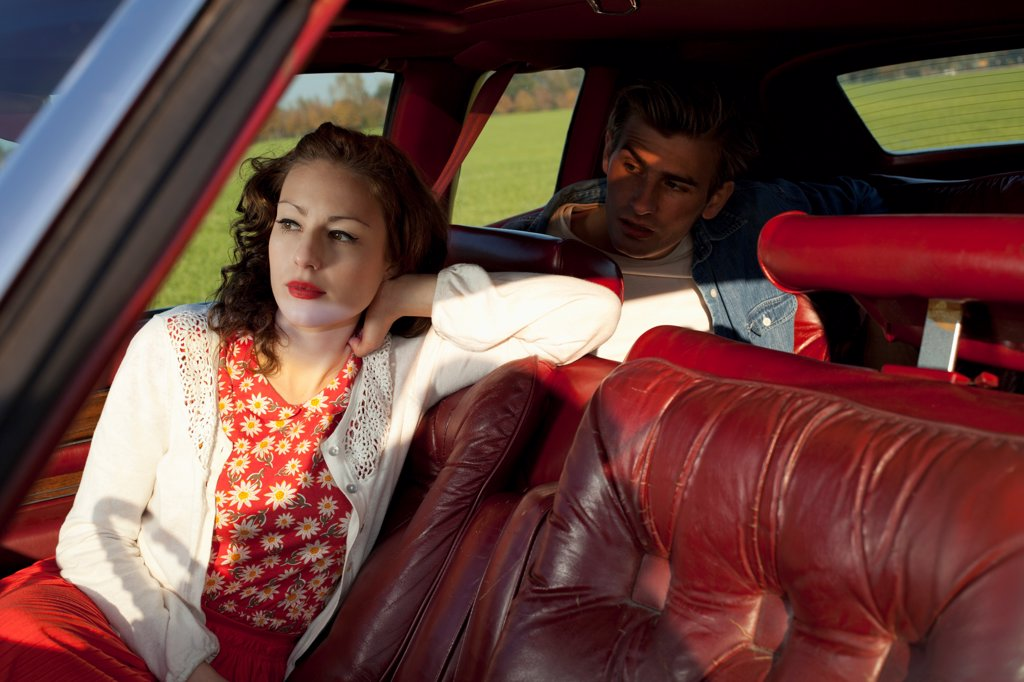 A rockabilly woman and man sitting in a vintage car : Stock Photo