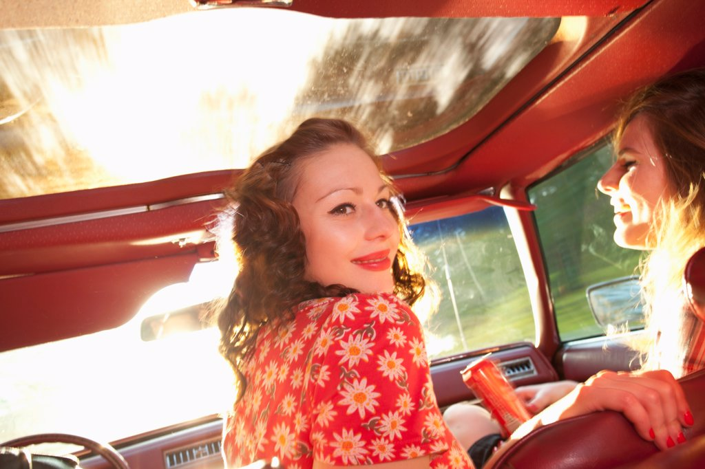Stock Photo: 1570R-141956 Two rockabilly women having fun in the front seat of a vintage car