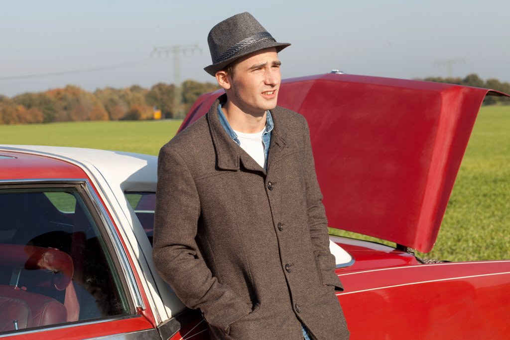 A young rockabilly man leaning against a vintage car in the country : Stock Photo