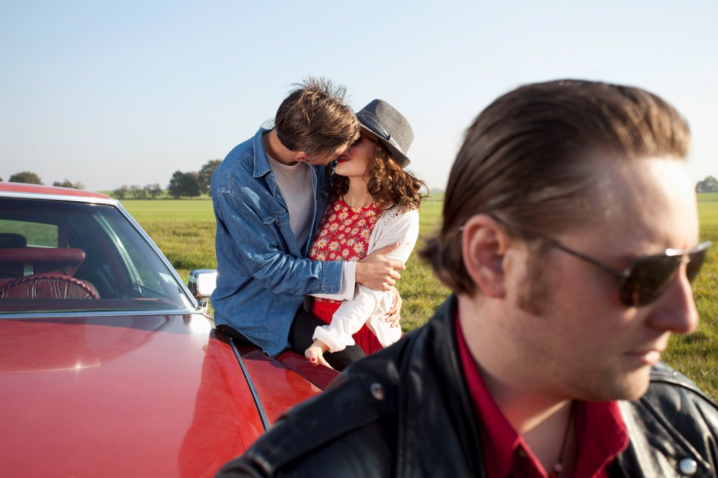 Stock Photo: 1570R-141965 A rockabilly couple kissing while leaning on a vintage car, man in foreground