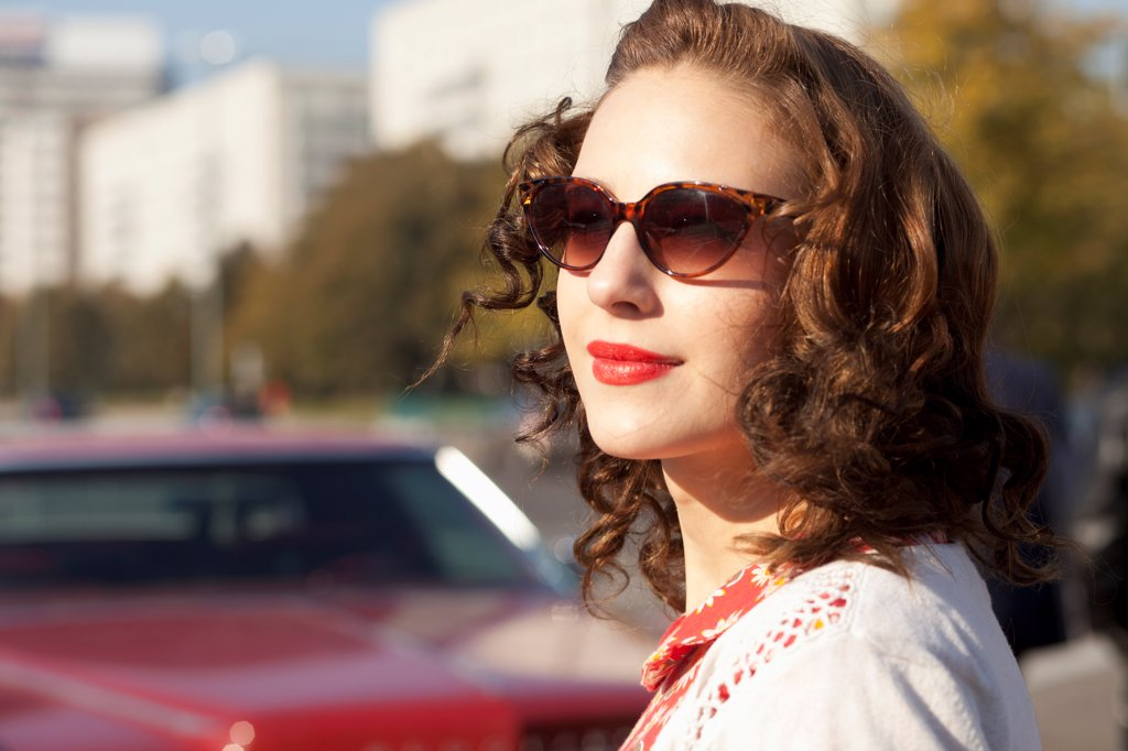 Stock Photo: 1570R-141968 A pretty rockabilly woman standing near a vintage care, focus on woman