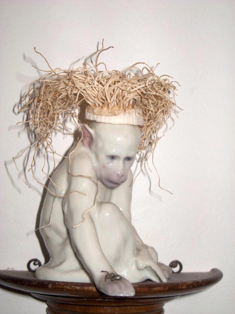 A ceramic monkey with straw hair : Stock Photo