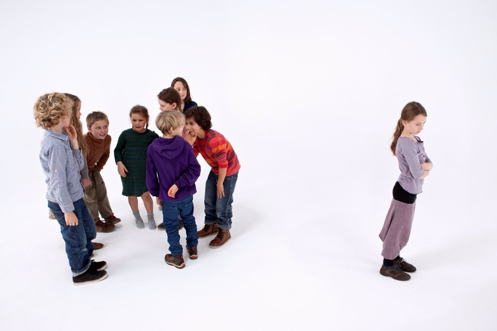 Stock Photo: 1570R-142554 A girl standing alone, arms crossed, while a group of kids gossip about her